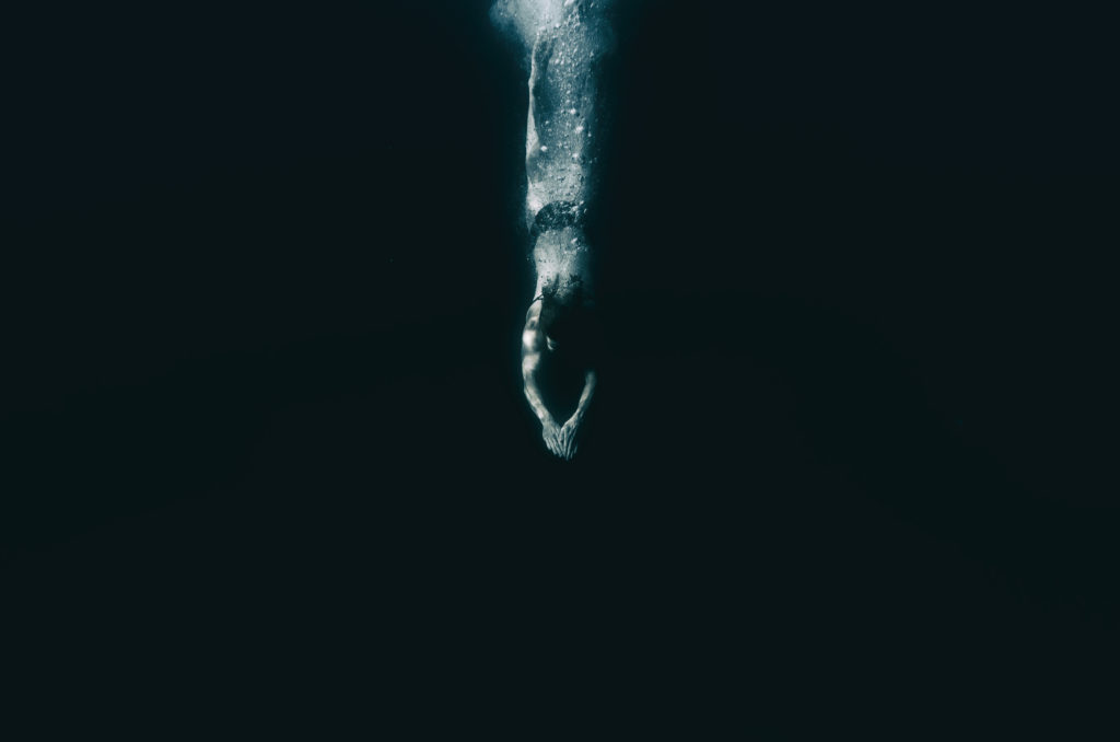 Person diving into dark water